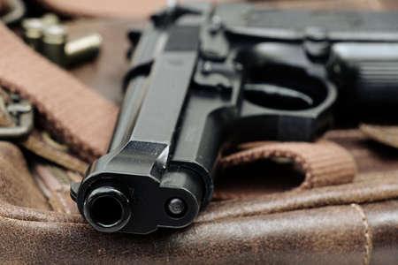 pistol: Semi-automatic handgun lying over a Leather handbag, 9mm pistol, Close-up Barrel