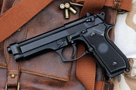 semi automatic: Semi-automatic handgun lying over a Leather handbag, 9mm pistol