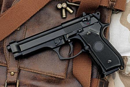 world war ii: Semi-automatic handgun lying over a Leather handbag, 9mm pistol, Process HDR detail