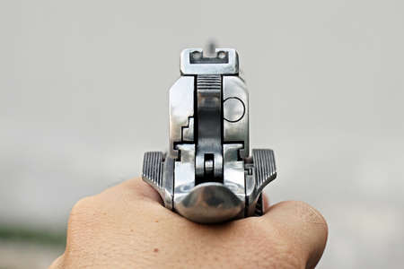 45 gun: Human hand holding gun, hand aiming a handgun, 45 pistol Stock Photo