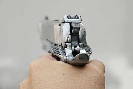 Human hand holding gun, hand aiming a handgun, 45 pistol photo