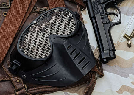 bb gun: Airsoft mask, Metal Mesh Shooting Face Mask, protection mask, Black Mask safety sport gun,  lying over a Leather handbag