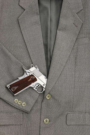 lobbyists: Semi-automatic handgun in business suits, 45 pistol. Stock Photo