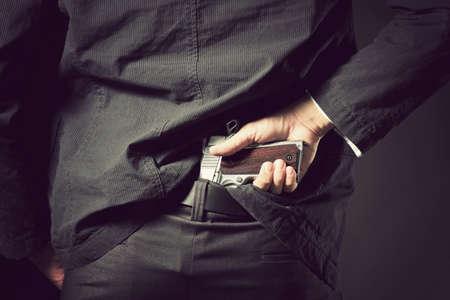 vengeful: A man, policeman or gangster concealing his gun behind his back