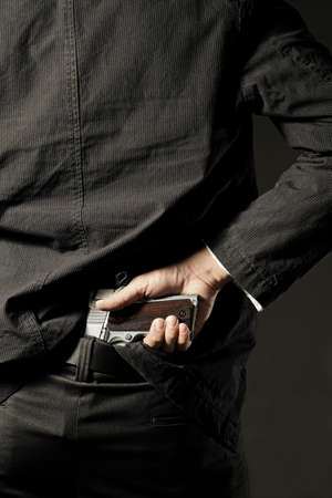 concealing: A man, policeman or gangster concealing his gun behind his back