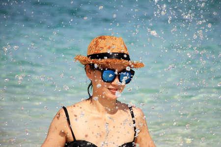 Young playful girl splashing on the beach, Woman with sunglasses in bikini.