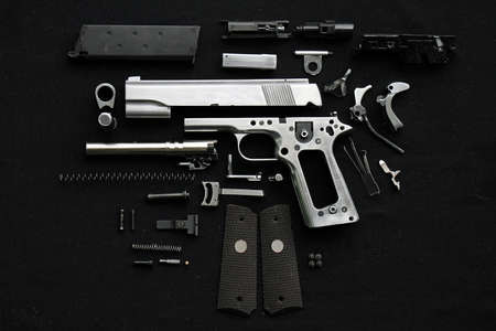 Disassembled handgun on black background,