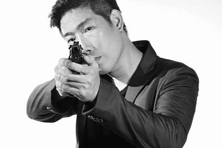 Asian Businessman aiming with handgun, Man in a suit preparing to shoot. Isolated on white. Semi-automatic handgun, 45 pistol. Stock Photo