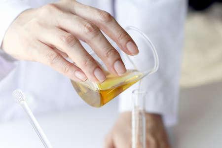 美容化粧品科学の策定とハーブ エッセンス、科学者注ぐオーガニック ・ エッセンシャル オイル、健康的な代替医療とスキンケアを混合します。