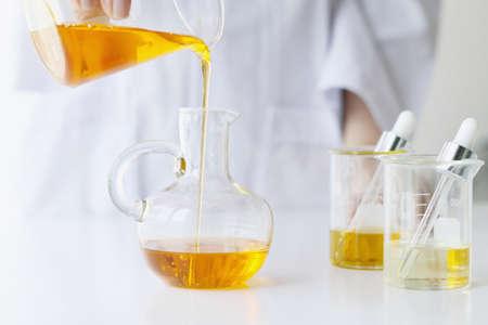 Beauty cosmetics sciences, Formuleren en mengen huidverzorging met kruidenessentie, wetenschapper gieten biologische essentiële olie, alternatieve gezonde geneeskunde.