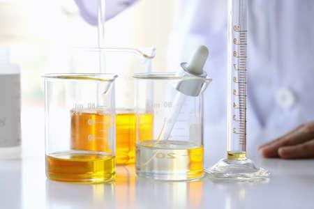 Ölgießen, Ausrüstungs- und Wissenschaftsexperimente, die Formulierung der Chemikalie für Medizin, organisches pharmazeutisches, Alternativmedizinkonzept. (Selektiver Fokus)