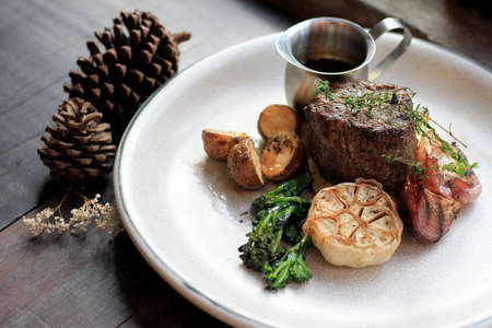 Beef rib eye steak with roasted potato and vegetables.