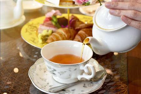 socializando: Verter el té de la tetera vintage a la taza, Inglés Tea Time.