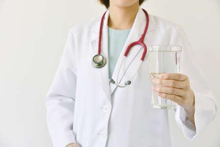 澄んだ水のガラスを保持している医師、医師は、健康に良い水を飲むお勧めします。 写真素材