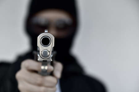 Criminal robber with aiming gun, Bad guy in hood holding pistol handgun. Stock Photo