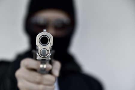 Ladrón criminal con pistola apuntando, Bad guy en capucha con pistola pistola.
