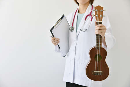 diagnose: Doctor hand holding ukulele (musical instrument), Music therapy concept. (Selective Focus)