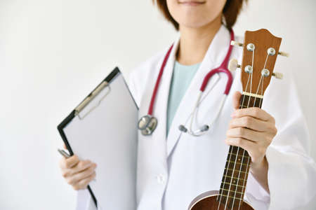 Doctor hand holding ukulele (musical instrument), Music therapy concept. (Selective Focus)