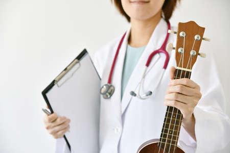 닥터 손을 잡고 우쿨렐레 (악기), 음악 치료 개념. (선택적 포커스)