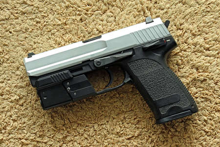 aluminum: Semi-automatic handgun on carpet background, 9mm pistol. Stock Photo