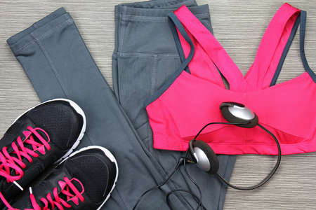 Headphones and smartphone to listen to music while working out at the fitness center. Matching clothes, Sport accessories and fashion, Healthy lifestyle.