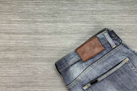 Men Fashion, Blue jeans on a brown wooden background. (Color Process)