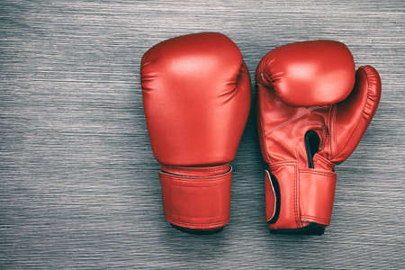 Pair of red leather boxing gloves on wooden background. (Color Processed) Stock Photo