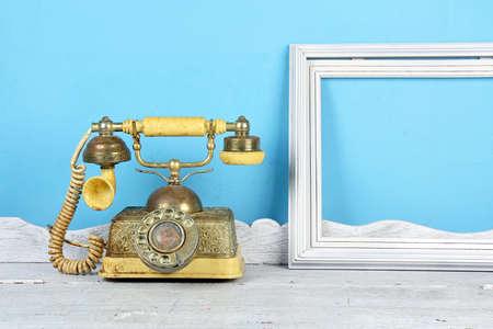 Luxury Vintage telephone and white frame over retro background.