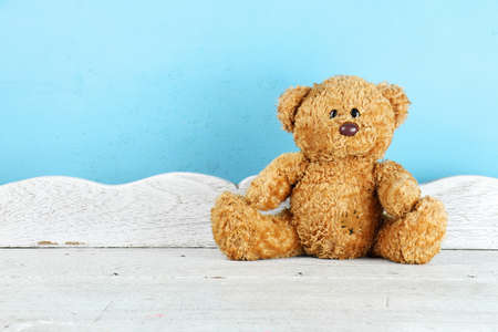 Teddy Bear toy alone on white wooden table in front of blue background. (Vintage Style Color)