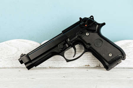 Weapon series. Modern U.S. Army handgun close-up on vintage wooden table background. pistols