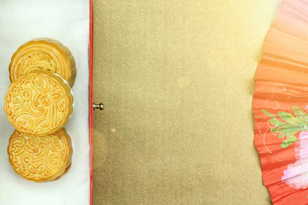 Chinese moon cake and red oriental chinese fan for celebrate in Mid autumn festival. (Moon cake day) Above angle. (Lighting Effect Processed) Stock Photo