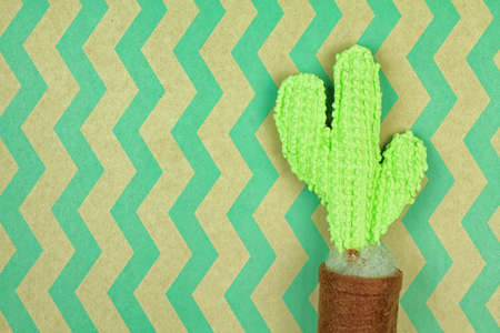 Knitted cactus on green wavy pattern brown paper, Home decoration, Eco-friendly concept. Stock Photo