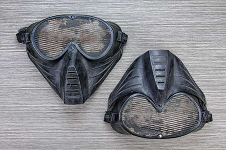 Airsoft BB gun metal mesh mask, Face safety protection from shooting sport game, Terrorist look mask on wood background.. (Grunge Effect Process)