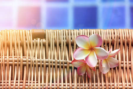 Tropical flowers (Frangipani) and woven basket on the side of a swimming pool, Spa and relaxing concept. (Lighting effect)