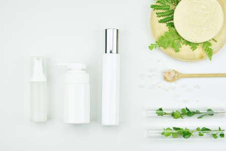 Kosmetische flessencontainers met groene kruidenbladeren, Leeg etiketpakket voor merkermodel, Natuurlijk organisch schoonheidsproductconcept. Stockfoto