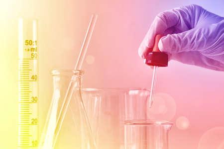 実験、科学者や化学者の手のための物質をドロップ新薬を発見研究開発コンセプト