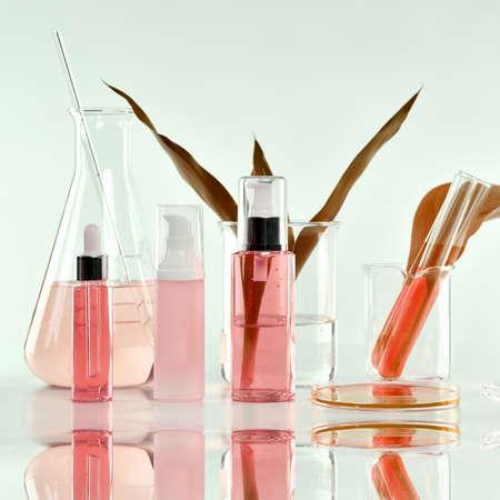 緑色のハーブの葉と科学的なガラス製品を持つ化粧品ボトル容器、モックアップをブランディングするためのブランクラベルパッケージ、研究し、