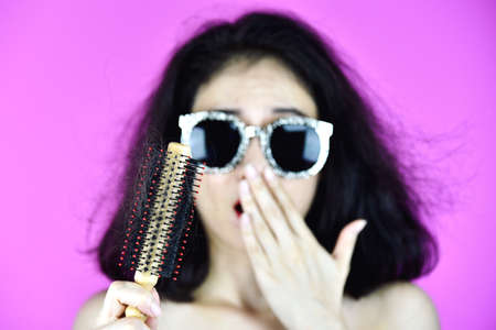 Hair fall problem, Woman with hair brush worry about hair loss.