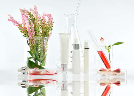 Cosmetic bottle containers with pink herbal leaves and scientific glassware, Blank label package for branding mock-up, Research and develop natural organic beauty skincare product concept.