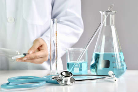 Doctor holding syringe with medicinal vaccine, Laboratory glassware, Drug research and development concept. (Selective Focus) Archivio Fotografico