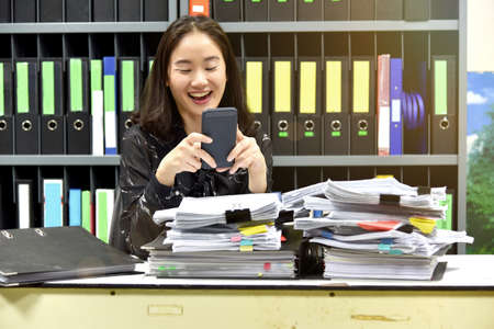 Lazy asian office woman using mobile smart phone in working time, Non productive employee.