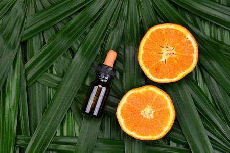 Cosmetics skincare with vitamin-c extract, Cosmetic dropper bottle containers with fresh orange slices, Blank label for branding mock-up, Natural Vitamin C beauty product concept. Stock Photo