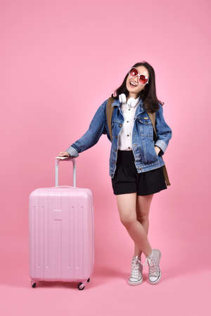 Smiling woman traveler holding pink suitcase and passport document over pink background, Holiday and travel concept. Stock Photo