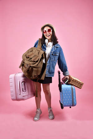 Smiling asian woman traveler carry lot of baggage, Happy tourist girl having cheerful holiday trip, Many luggage, suitcase and backpack, Bag deposit service.