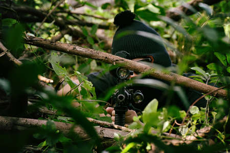 Soldiers aiming target and holding his rifles hidden ambushed, Army sniper camouflage in forest, Battle in the woods.