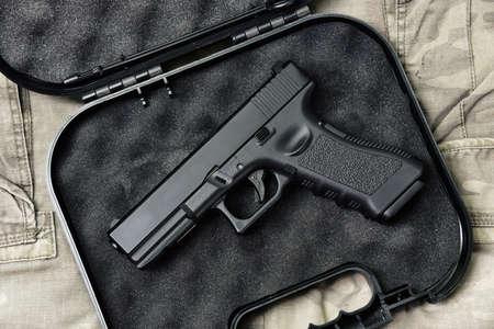Pistol 9mm, Gun weapon series, Police handgun close-up on camouflage background.