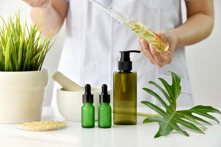 Natural skincare cosmetics research and development concept, Doctor formulating new beauty products from organic natural plants, Pharmacist mixing extract essence substance in test tube with container package.
