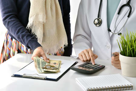 Hospital and medical expense, Doctor and woman patient calculate on disease treatment fee charges, Health insurance concept.