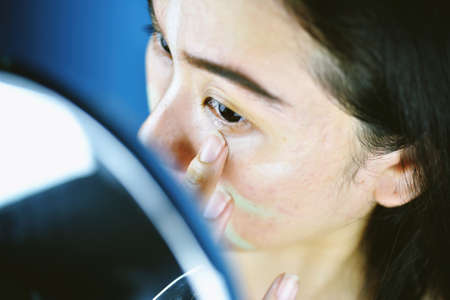 Asian woman applying cosmetics makeup and using color correction concealer, Learning doing self makeup. Stock Photo