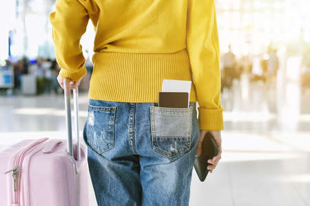 Traveller standing with a luggage at airport terminal, Passenger walking to departure check-in counter, Tourist arrive at destination, Travel concept. Standard-Bild